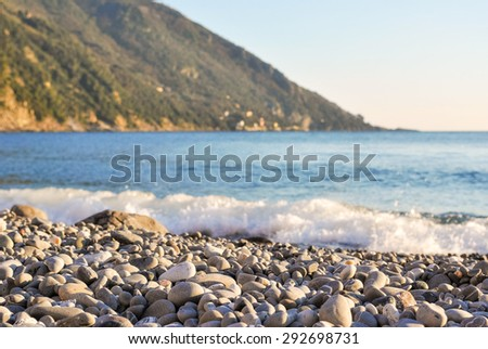 Pebbly beach in a shore, with the sea in background
