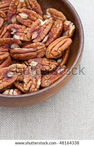 Pecan nuts in an old wooden bowl - stock photo