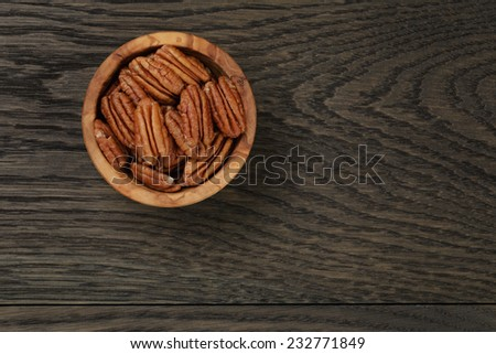 pecan nuts in olive wood bowl on oak table, rustic style - stock photo