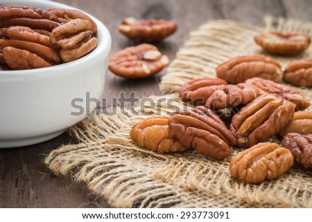 Pecan nuts on sackcloth and bowl   - stock photo
