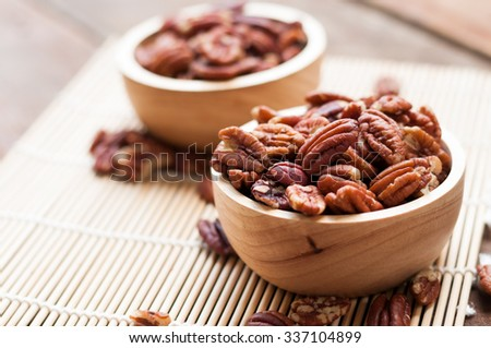 pecan nuts, on wooden board - stock photo
