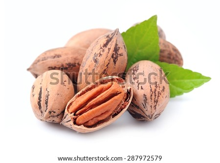Pecan nuts with leaves close up on white background - stock photo
