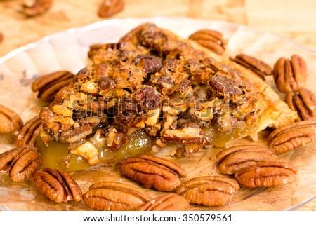 Pecan pie slice closeup with pecans on wooden background. - stock photo