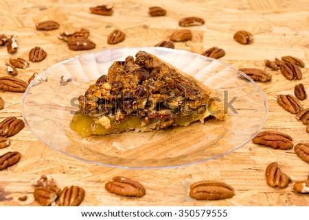 Pecan pie slice with pecans on wooden background - stock photo