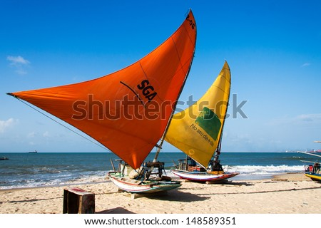"""PECEM, BRAZIL - MARCH 18 - traditional fishing boats, also called """"jangada"""" dries their sails on the beach. Pecem beach, Brazil on March 18, 2012. - stock photo"""