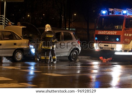 PECS, HUNGARY - DEC. 01: car crashed. Firefighter try to help the victim of car accident on Dec. 01, 2010 on Road 6 in Pecs, Hungary. - stock photo