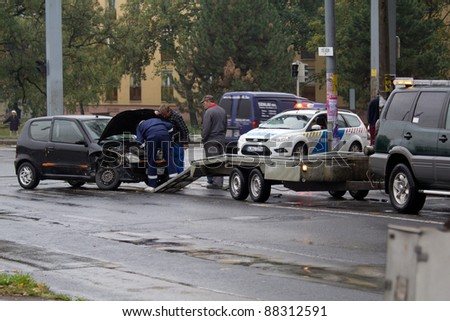 PECS, HUNGARY - OCT. 21: car crashed. Repairman try to help the victim of car accident on Oct 21, 2011 on Road 6 in Pecs, Hungary. - stock photo