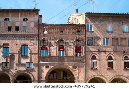 Peculiar windows on Renaissance buildings facades in Bologna downtown - stock photo