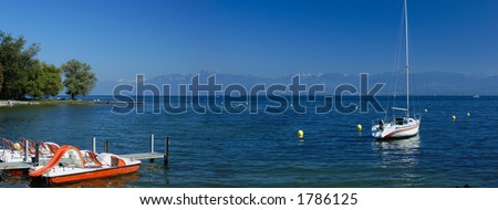 Pedalos stand empty and a yacht rides at mooring as the first snow dusts the distant peaks. Panoramic view across Lac Leman (Lake Geneva) towards the Alps in September. Space for text in the sky.