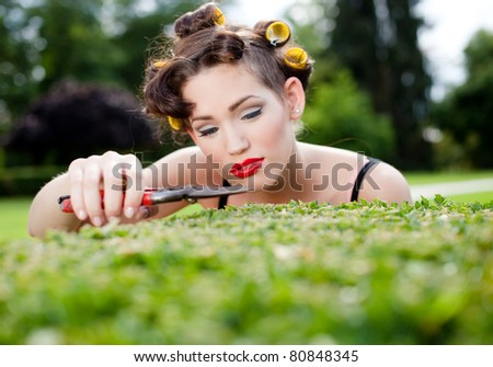 Pedantic housewife gardening. She's cutting the bush to perfection - stock photo