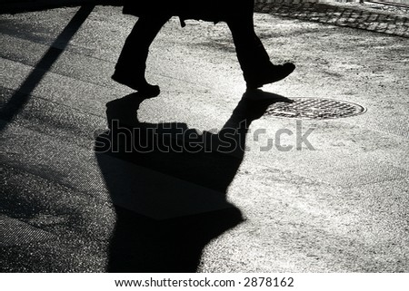 Pedastrian crossing the street by passage. Silhouette. - stock photo