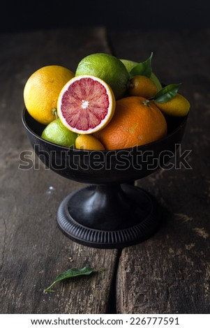 Pedestal bowl of assorted fresh citrus fruit with a halved blood orange displayed at the front on a rustic wooden background with shadows - stock photo