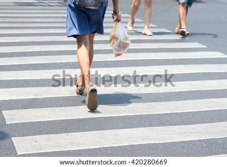 pedestrian across crosswalk on the road - stock photo
