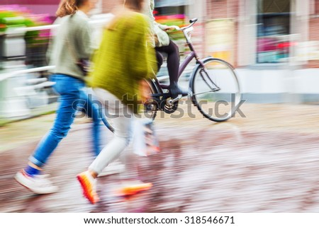 pedestrian and bicycle rider in motion blur on a rainy day in the city - stock photo