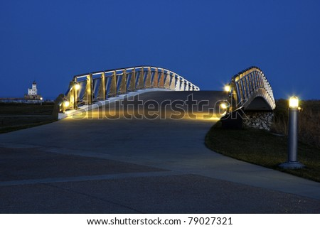 Pedestrian bridge by the Lakefront in Milwaukee. Milwaukee Breakwater Lighthouse in the background. - stock photo