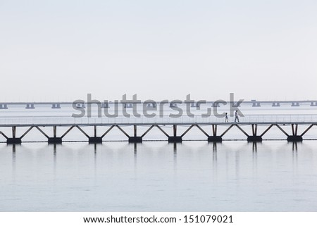 Pedestrian bridge in Park of the Nations with the Vasco da Gama bridge on the background, Lisbon, Portugal. - stock photo