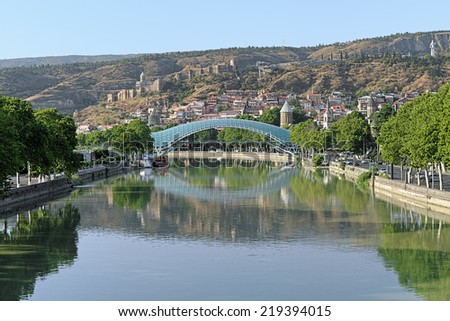 Pedestrian Bridge of Peace over the Kura River, Narikala Fortress and Kartlis Deda Monument in Tbilisi, Georgia - stock photo