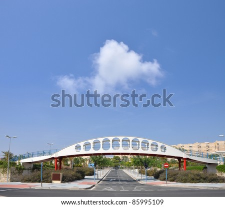 Pedestrian Bridge over Empty Street with Traffic Symbols in Urban City Neighborhood on Blue Sky Day