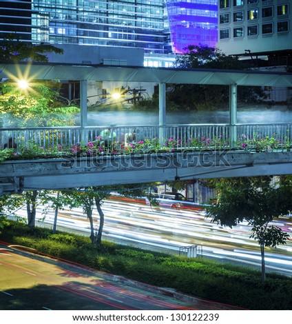 Pedestrian bridge over night street - stock photo