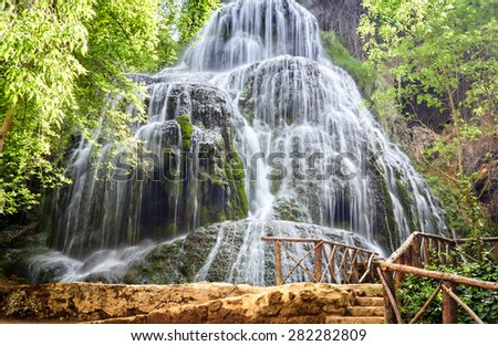 Pedestrian bridge over river waterfall in the woods green crystal. - stock photo