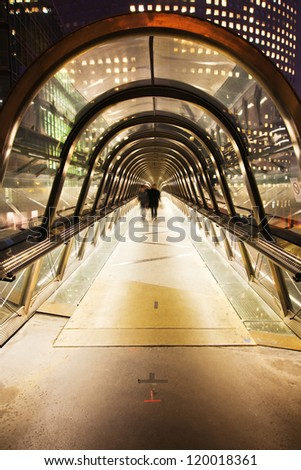 pedestrian bridge under a glass dome in La Defense, Paris, with blurred business people walking at the end of the tunnel - stock photo