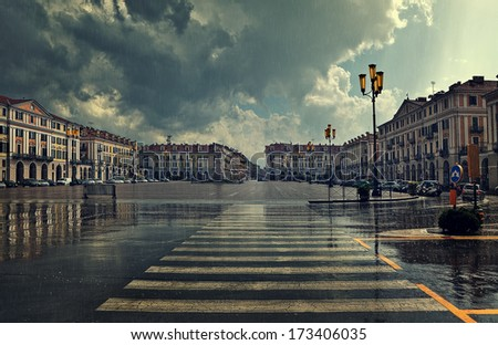 Pedestrian crossing and big plaza at city center under cloudy sky at rainy day in Cuneo, Italy. - stock photo