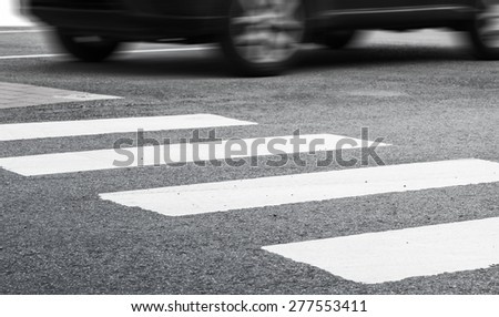 Pedestrian crossing road marking and fast moving car, photo with selective focus and shallow DOF - stock photo