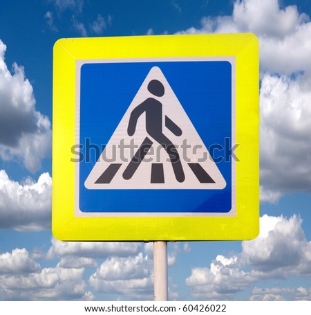 Pedestrian crossing sign against the sky