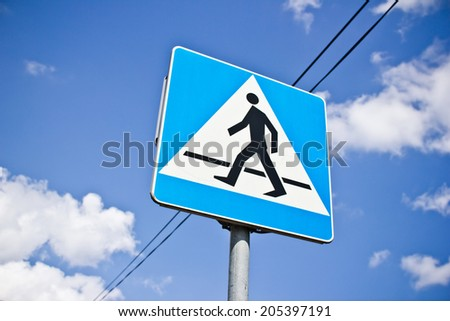 Pedestrian crossing sign with blue sky in background.  - stock photo