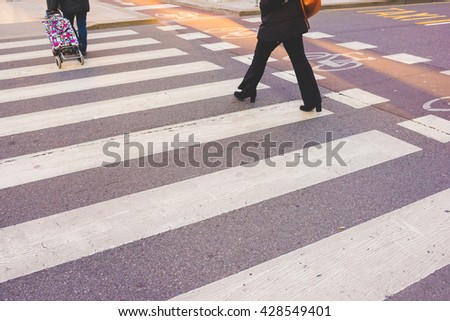 Pedestrian crossing sing with people walking on it - stock photo
