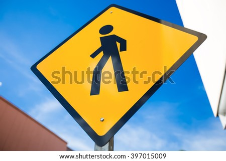 Pedestrian crossing street sign at the street on blue sky background