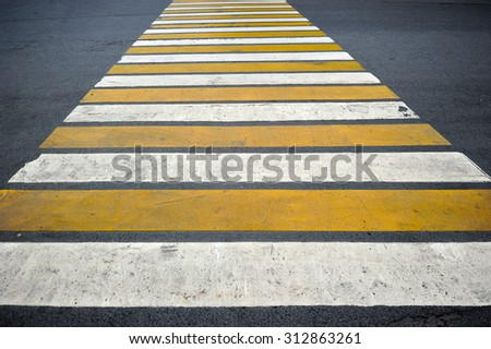 pedestrian crossing the road consists of white and yellow stripes - stock photo