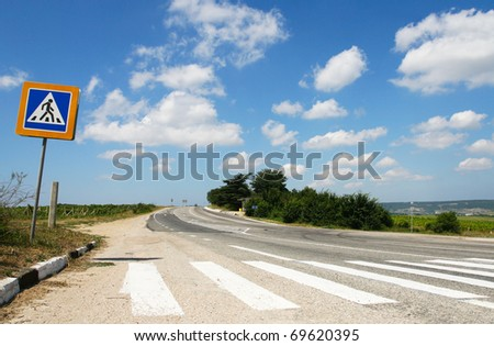 Pedestrian crossing with a sign on a country road - stock photo
