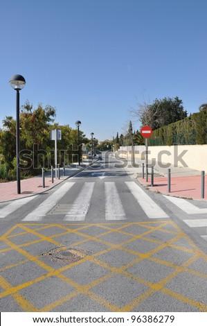 Pedestrian Crosswalk Wrong Way Traffic Sign on Modern Mediterranean Suburban Neighborhood Street in Spain Europe - stock photo