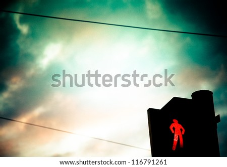 Pedestrian red light opposite to evening sky - stock photo