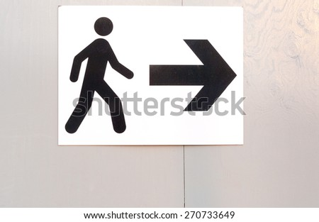 Pedestrian route direction icon and direction on white painted notice board