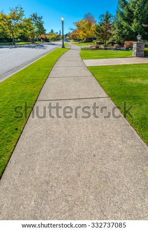 Pedestrian sidewalk at the empty street with nicely trimmed bushes, green fence in a nice neighborhood in the suburbs of Vancouver, Canada. - stock photo