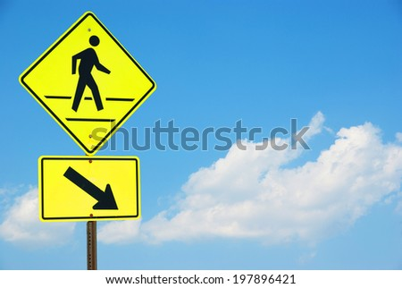 Pedestrian sign with a person walking on yellow with a blue sky background