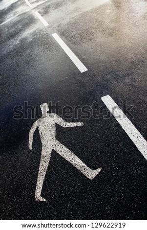 Pedestrian street sign on a wet dark asphalt floor. - stock photo