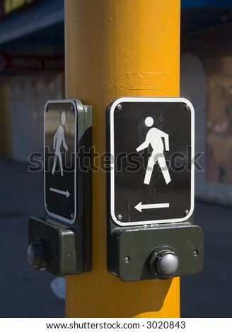 Pedestrian walk button on a yellow pole. - stock photo