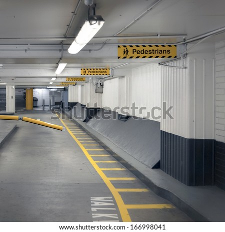 Pedestrian walkway and signage in an undercover parking garage. - stock photo