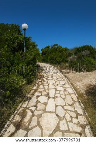 Pedestrian walkway, lampposts along Mediterranean sea coastline in Corfu, Greece - stock photo