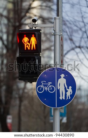 Pedestrian walkway sign with a red traffic light - stock photo