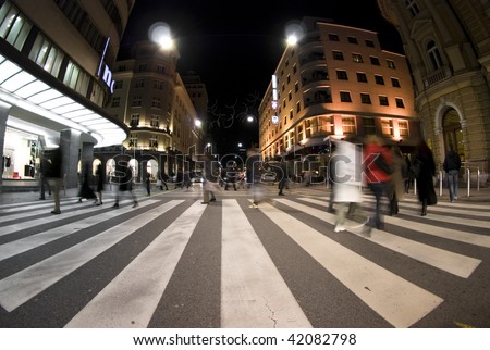 Pedestrian zebra crossing on busy street at night - stock photo