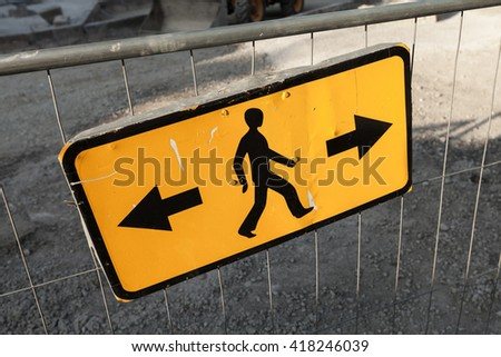 Pedestrians bypass directions. Yellow road sign on construction site border - stock photo