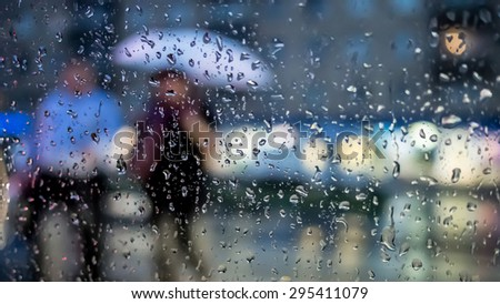 Pedestrians crossing the street in the rain, view through a rainy window - stock photo