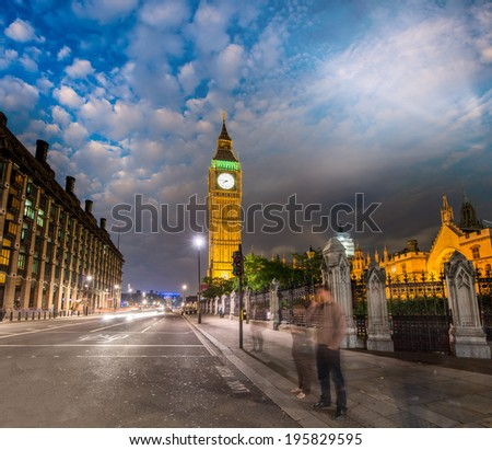 Pedestrians enjoying night in Westminster with Big Ben lights. - stock photo