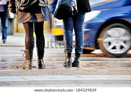 Pedestrians on zebra crossing after the rain. Car passing. - stock photo