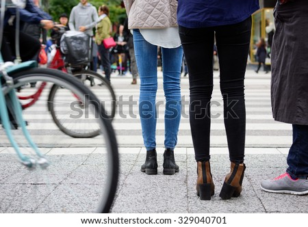 Pedestrians waiting to cross street. Bikes out of focus. - stock photo