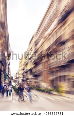 Pedestrians walking and talking and bikers riding bikes - rush hour and busy traffic in Italian city Palermo. Radial zoom effect defocusing filter applied, with vintage instagram look. - stock photo